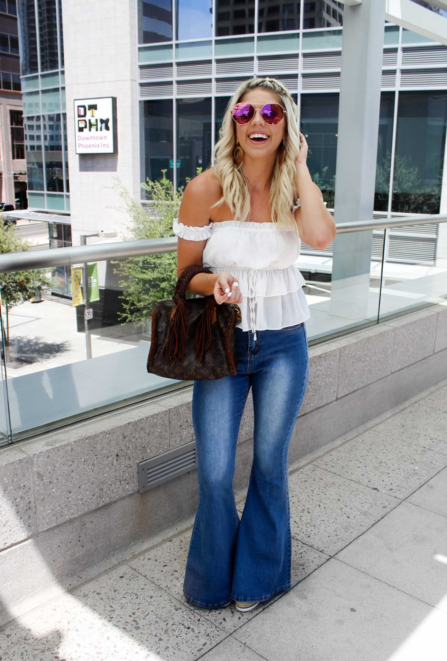 Erin Elizabeth of Wink and a Twirl shares this Shop Oh Boutique look with bell bottom jeans and a white off the shoulder crop